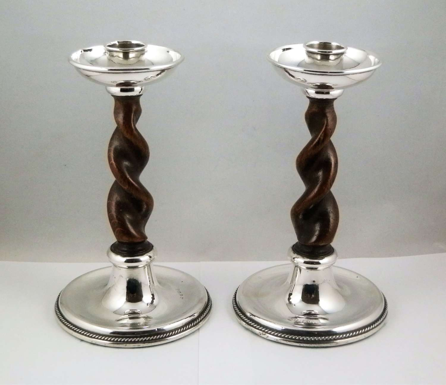 An arts and crafts pair of barley twist silver candlesticks, A. E. Jo